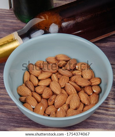 side view of almond in a bowl and a bottle of beer on rustic background