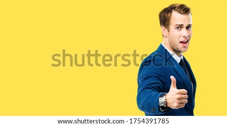 Wide composition picture - excited businessman showing thumbs up like hand sign gesture, in blue confident suit, over yellow color background. Handsome happy man. Copy space for some text.