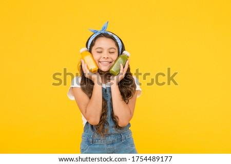 Fresh smoothie. Girl drinking orange fresh juice smoothie. Vegetarian concept. Hand crafted smoothie recipe. Fruit energy. Smiling kid hold smoothie bottles. Healthy food. Vitamin nutrition. #1754489177
