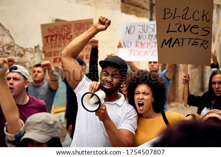 Displeased black couple shouting while marching with group of people on  anti-racism protest. Royalty-Free Stock Photo #1754507807
