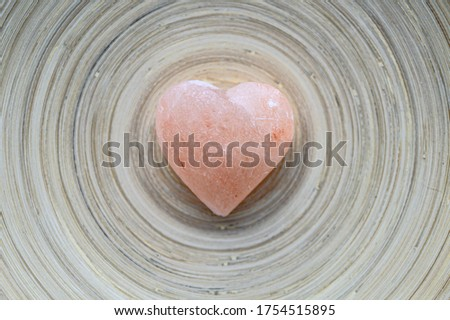 Pink stone heart with rock stones in background. Symbol of love.