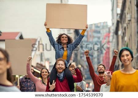 Group of multiethnic people on street holding blank cardboard placard celebrating victory during a protest. Group of content men and smiling women marching through a city. People protesting on road.