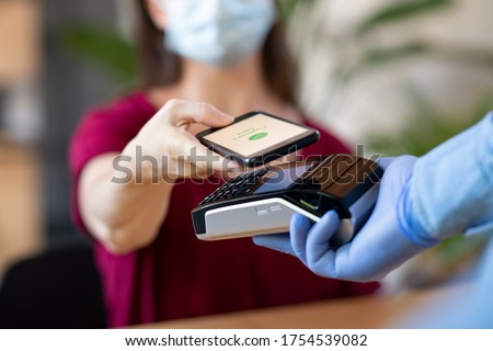 Cashier hand holding credit card reader machine and wearing disposable gloves while client holding phone for NFC payment. Woman wearing face mask while paying with smartphone during Covid-19 pandemic. #1754539082