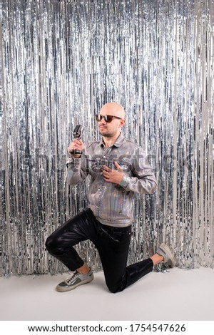 Picture of beautiful caucasian man without hair with black sunglasses in a shiny shirt, black leather pants and grey sneakers sings in a small silver microphone isolated on silver glitter background.