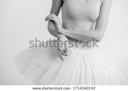 Black and white picture of beautiful young fit female doing sport exercises in big bright white studio