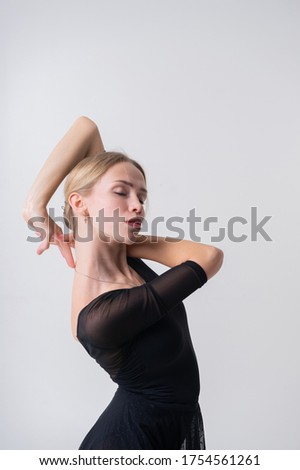 Picture of caucasian girl with long fair hair, pretty face in black swimsuit and white skirt for ballet engaged art gymnastic