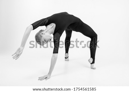 Black and white picture of attractive young female gymnast with pale skintraining calilisthenics exercise on a white studio background