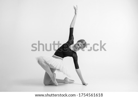 Black and white picture of slender little ballerina dances and enjoys it