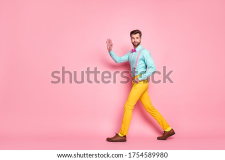 Full length profile photo of handsome guy trend look walk meeting red carpet celebrity waving hand wear shirt suspenders bow tie yellow pants footwear isolated pastel pink color background #1754589980