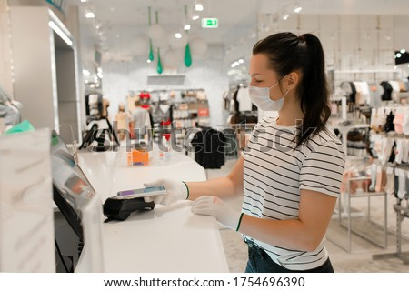 Young girl a cashier in a mask and gloves in a clothing store because of the covid-19 virus. A woman in a medical mask buys clothes. Girl pays for purchases in the store with a card #1754696390
