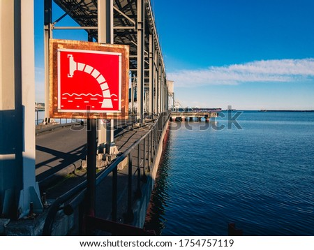 A water intake sign for a fire engine is fixed on the metal support of a sea pier against the backdrop of a beautiful landscape with turquoise sea water and a blue cloudy sky on a sunny day. #1754757119