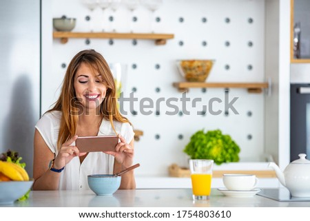 Woman in the kitchen taking photo of prepared breakfast. Beautiful woman in kitchen using mobile phone. Ready to make her own recipe book. Woman taking a picture of breakfast on her kitchen table