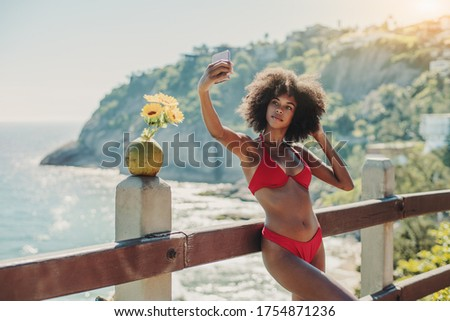 A sexy young Brazilian female is taking selfie using a smartphone while leaning against a wooden fence on a resort near the beach, with coconut and flowers near her; African-American girl taking pics