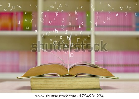 Open book on the table and English alphabet Floating above the book in the library and blur bookshelf background.