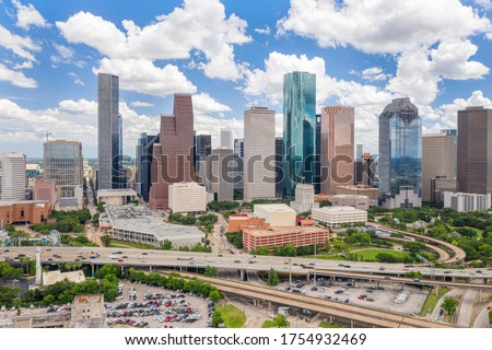Sky drone view of downtown Houston during day with cityscape and highway in view.