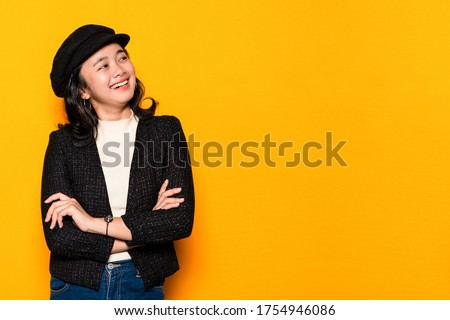 Asian young woman smiling with folded hands on yellow background