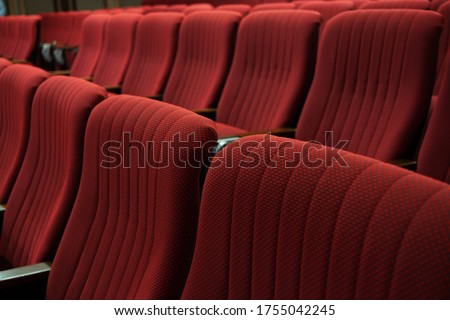 Theater closed due to Coronavirus. Movie theater, stadium, stage, performance center closure under COVID-19 global pandemic. Empty dark red velvet seats in theater, cinema, conference and concert. #1755042245