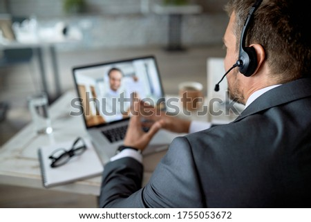Close-up of entrepreneur using laptop while having online business meeting in the office.  Royalty-Free Stock Photo #1755053672