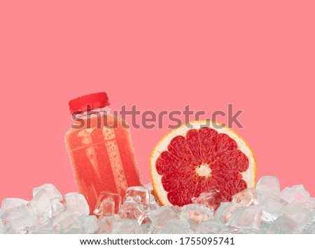 Close up one plastic PET bottle full of fresh pink grapefruit juice and cut half slice on ice cubes isolated on pink background, low angle side view #1755095741