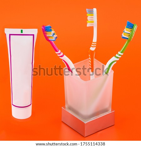 bright and beautiful comfortable toothbrushes in a glass with toothpaste #1755114338