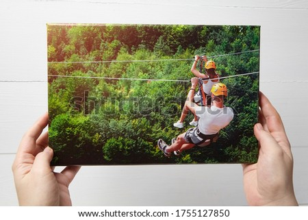 Canvas print. Photo with gallery wrap method of canvas stretching on stretcher bar. Woman hangs a color travel photography (with people on zip line) on a white wooden wall