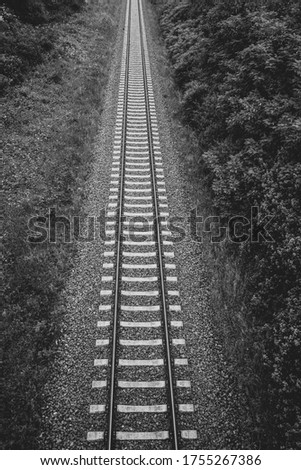 Railway tracks on a railway track bed lead through the picture