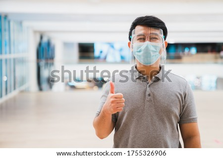Young asian man wear face shield and mask smiling in shopping mall Royalty-Free Stock Photo #1755326906