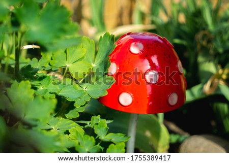 Garden ornaments in amongst the flowers on a sunny day. These metal ornamental toadstool mushrooms add a splash of red colour against the green foliage. #1755389417