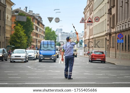 Policeman directing traffic in the city. Traffic police adjusts traffic at intersection of  avenue, rush hour. Police officer regulating traffic on city streets.  #1755405686