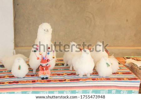 A picture of souvenirs of white alpacas on a colorful cloth