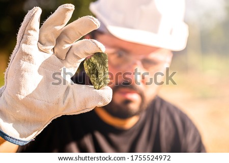 miner holding gold nugget, point focus on the gemstone. Mineral exploration concept, Minnesota, United States #1755524972