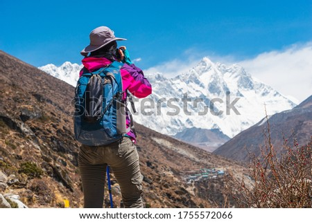 Young woman trekker taking picture while trekking in Everest Base Camp, Himalaya mountains range in Nepal, Asia