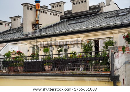 Terrace in old house under pitched roof with potted flowers in Krakow, Poland. Building facade with lot of flower pots. Outside Patio for relax