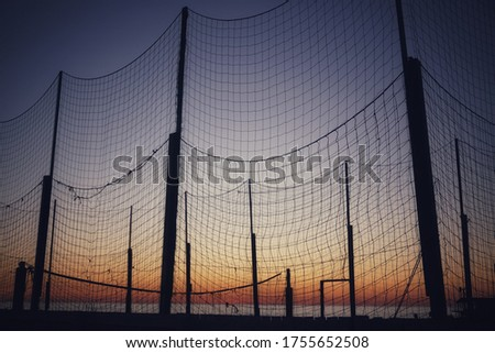 Net of a beach volleyball court at sunset #1755652508