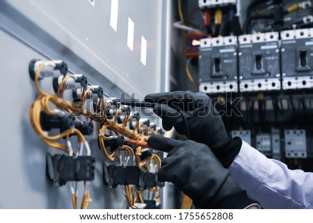 Electrical engineer using digital multi-meter measuring equipment to checking electric current voltage at circuit breaker in main power distribution board. Royalty-Free Stock Photo #1755652808