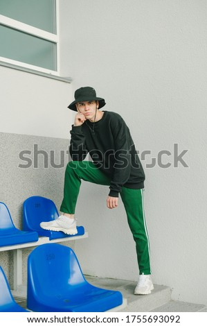 Trendy street portrait of stylish guy in casual clothes and panama hat posing at camera in sports stands on gray wall background. Street fashion photo. Royalty-Free Stock Photo #1755693092