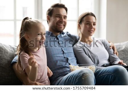 Happy parents with little daughter watching tv, comedy movie or soccer match together, sitting on cozy couch in living room, enjoying leisure time at home, family eating popcorn snacks