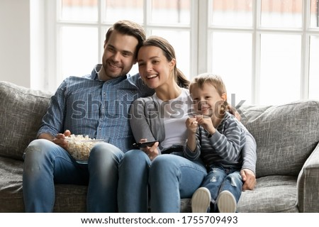 Happy young parents with little son watching tv together, sitting on cozy couch in living room, smiling mother holding remote controller, family eating popcorn snacks, watching movie, having fun