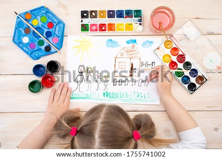 A child draws a birthday card with his family. The drawing was made by a child using color paints. A happy family. Children's drawing. View from above.