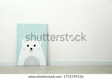 Adorable picture of bear on floor near white wall, space for text. Children's room interior element