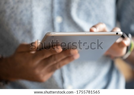 Close up hands African man holding digital tablet device. E-commerce websites buy in internet on-line stores usage, typing e-mail to client, reading sending message to friends, e-date website concept Royalty-Free Stock Photo #1755781565