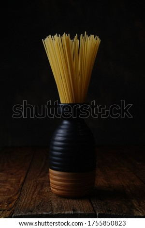 A raw spaghetti in a pot. This picture take with a stilllife photography, lowkey, and dark backgorund concept
