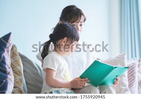 Mother and daughter sitting on the sofa and reading a picture book