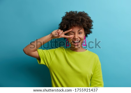 Charming friendly African American woman makes peace sign over eye, smiles broadly and feels positive emotions, sends good vibes, wears bright green t shirt. People, emotions, summertime concept #1755921437