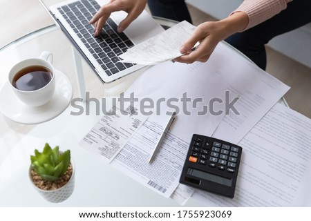 Top view close up woman calculating bills, money, loan or rent payments, using laptop, online banking service, sitting at table, female holding receipt, planning budget, managing expenses, finances Royalty-Free Stock Photo #1755923069