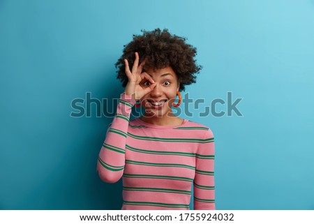Portrait of funny cheerful Afro American woman makes okay gesture over eye, completely agrees with suggestion, smiles broadly, wears striped sweater, isolated on blue background, Everything is fine
