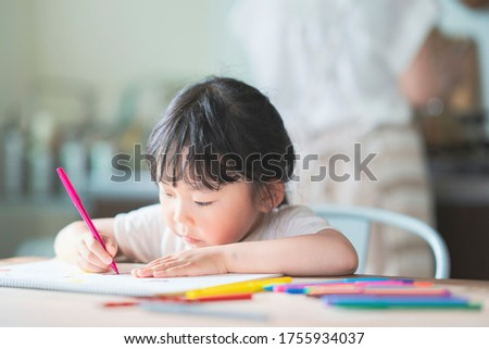 Asian girl drawing with colorful pens at the dining table at home