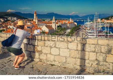 Pretty woman taking a picture with phone from the castle. Happy traveler woman with smartphone, taking travel images in Trogir old town from the tower of Kamerlengo castle, Dalmatia, Croatia, Europe