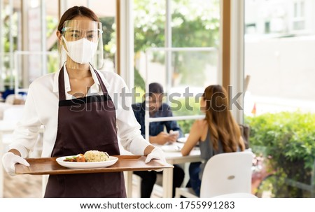 Portrait attractive asian waitress wear face mask and face shield holding food tray to serving meal to customer with custome in background. New normal restaurant concept. #1755991283