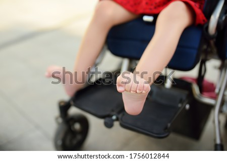 Disabled girl sitting in wheelchair. Close up photo of her legs spasticity muscles . Child cerebral palsy. Disability. Inclusion. Family with disabled kid. Family with disabled kid. #1756012844